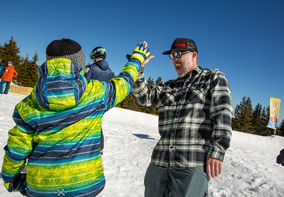 Shaun Cattanach, winner of PSIA-AASI's 2019 Distinguished Service Award, high-fives a child who learned to snowboard at Interski 2019 in Bulgaria.
