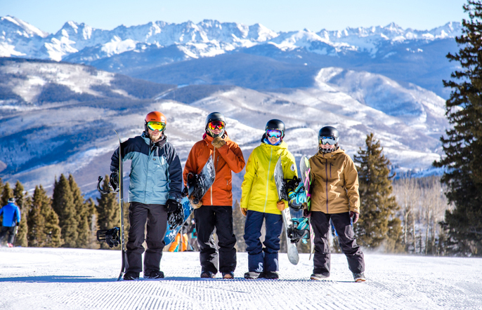 A group of four snowboarders stands at the top of a run holding their boards