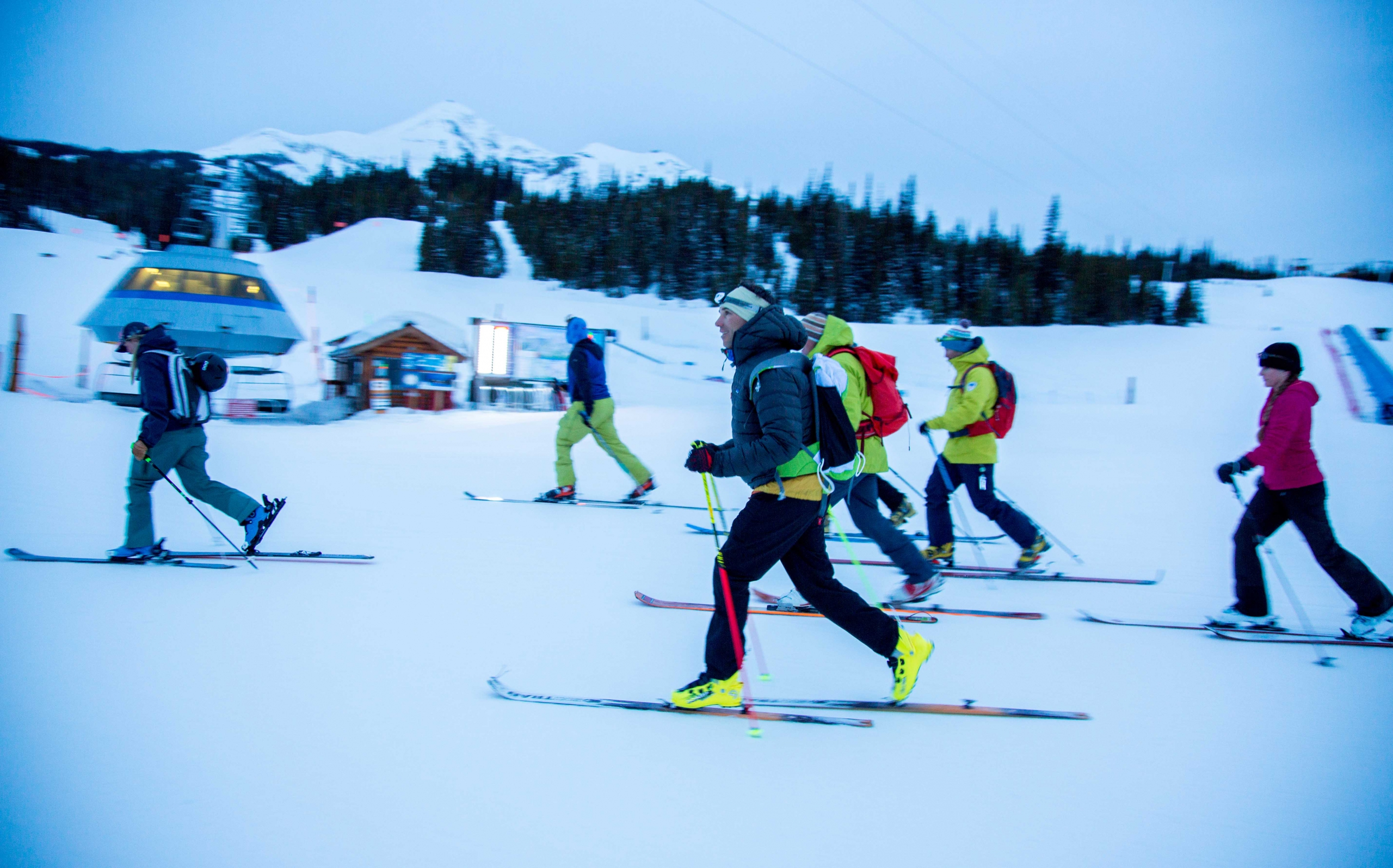 PSIA-AASI CEO Nick Herrin skins up a slope with a group of skiers