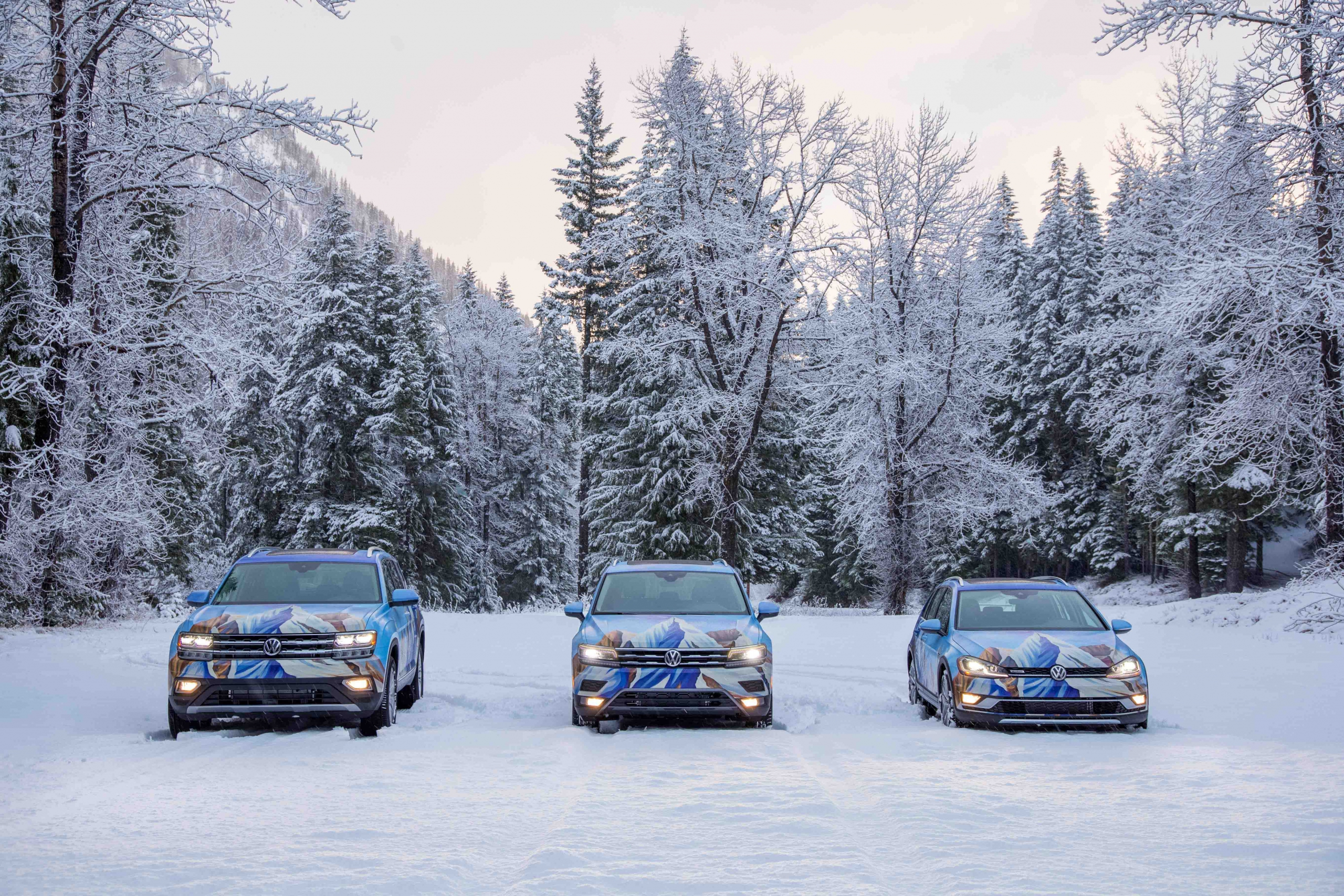 The PSIA-AASI custom painted Atlas Tiguan and Alltrack are parked in a snow covered parking area facing the camera