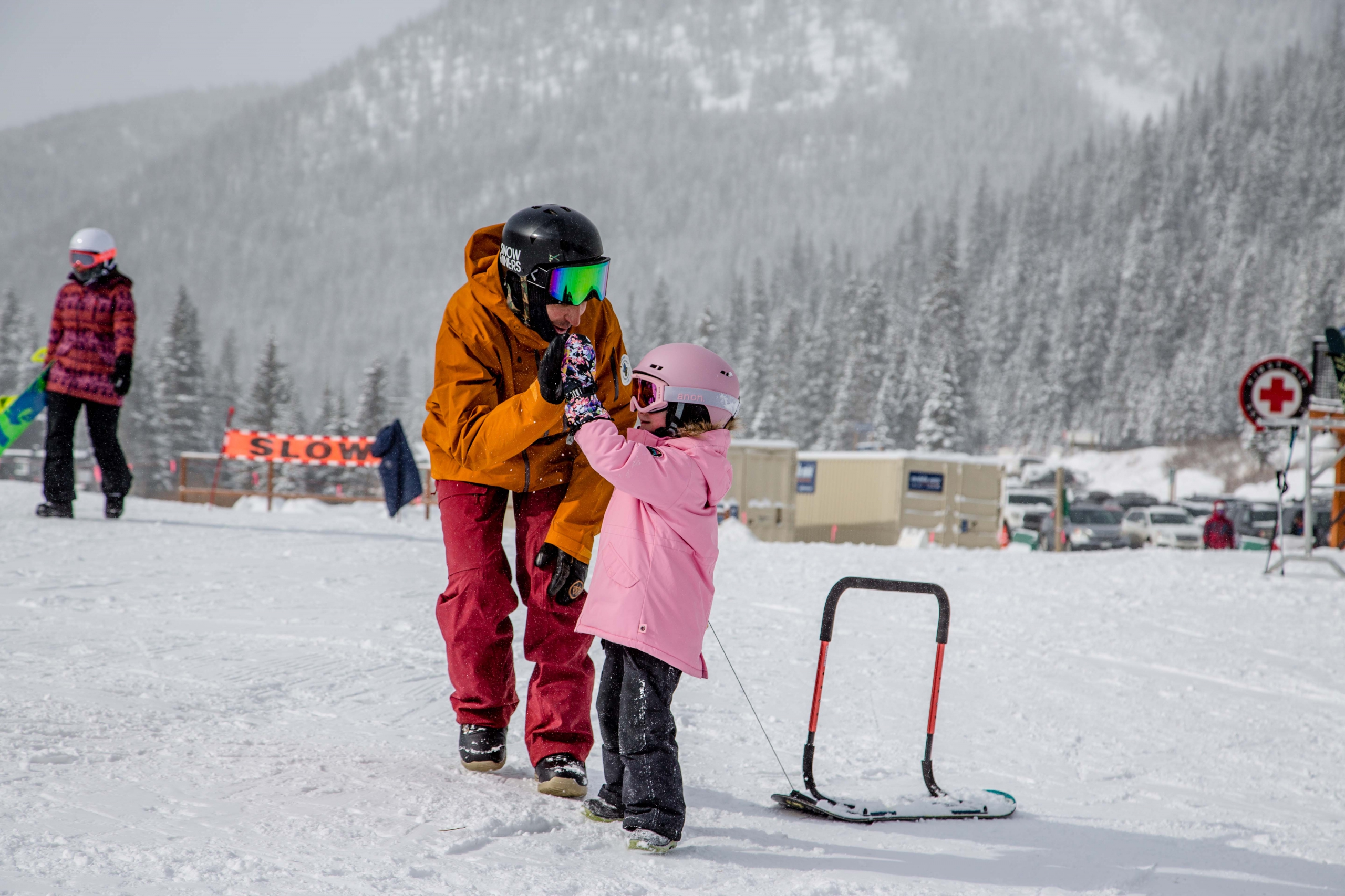 AASI Team Member Tony Macri high fives a young student in a snowboard lesson