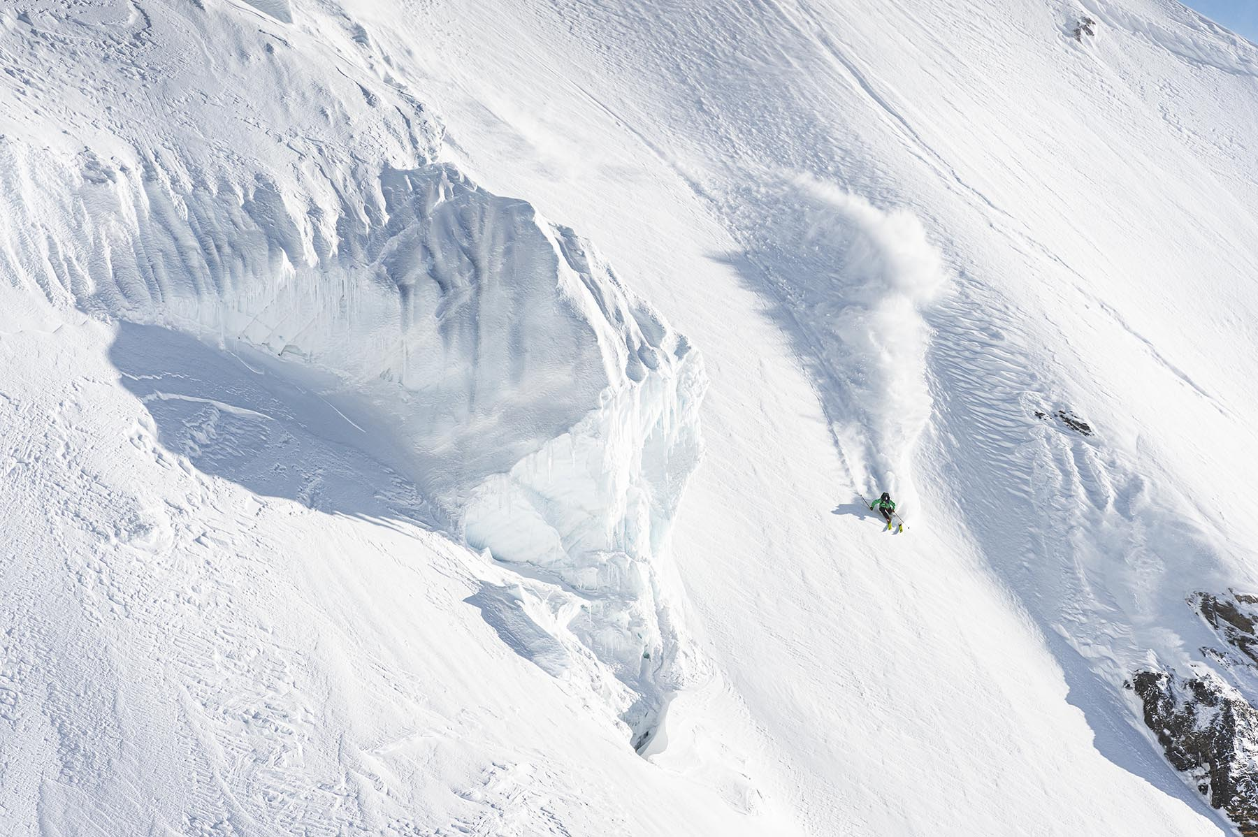 A skier descends a steep off-piste slope on Faction skis