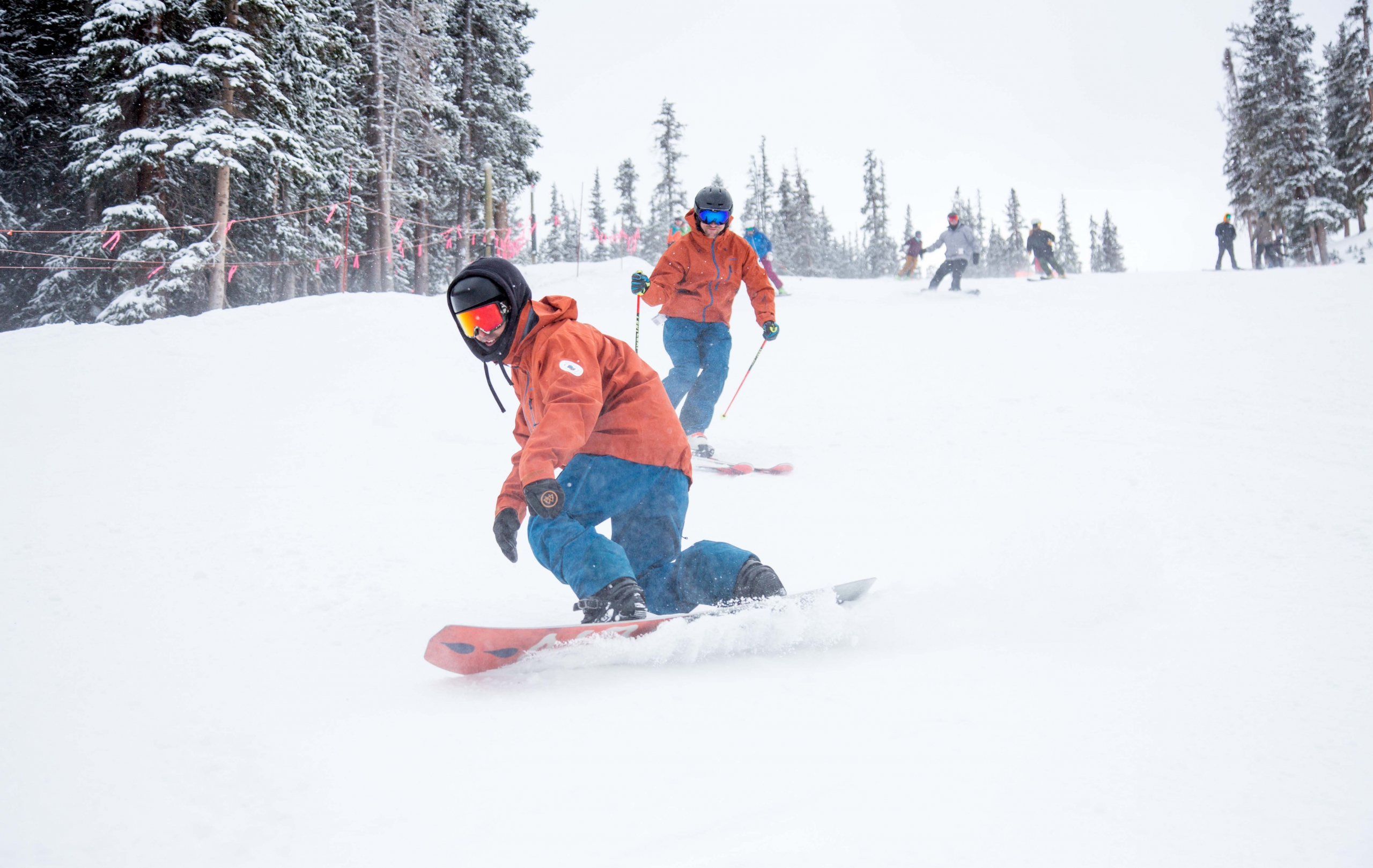 PSIA-AASI National Team members snowboard and ski down the slope at A-Basin