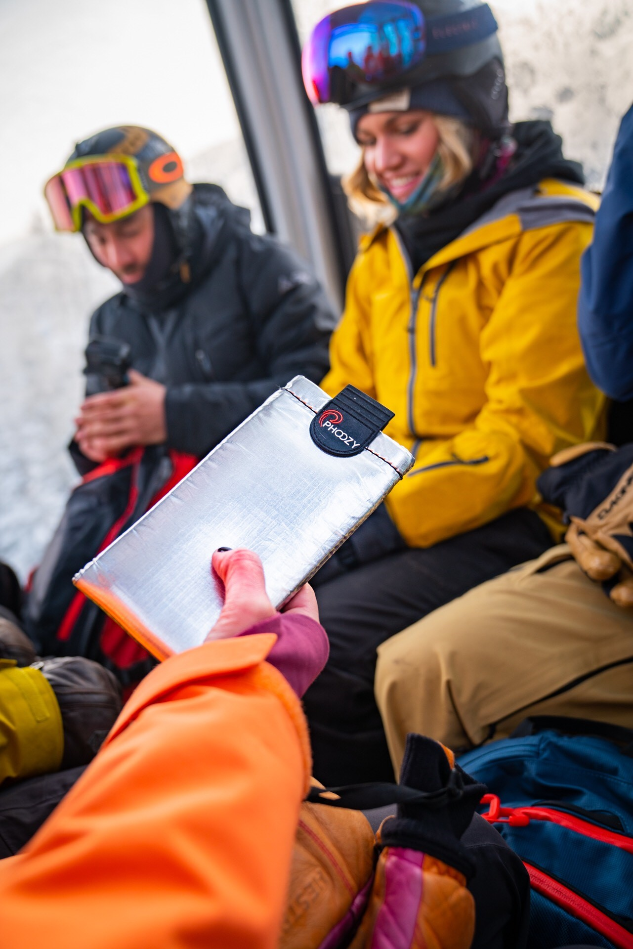A gondola rider holds up their phone encased in a phoozy case