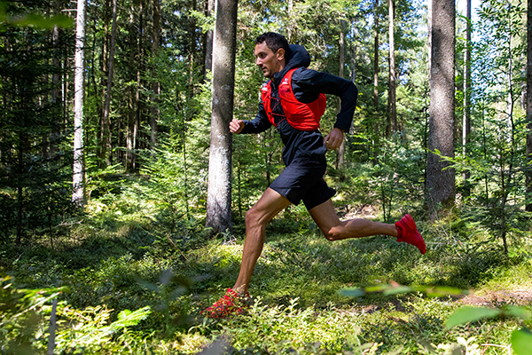A Salomon trail runner sprints in the woods