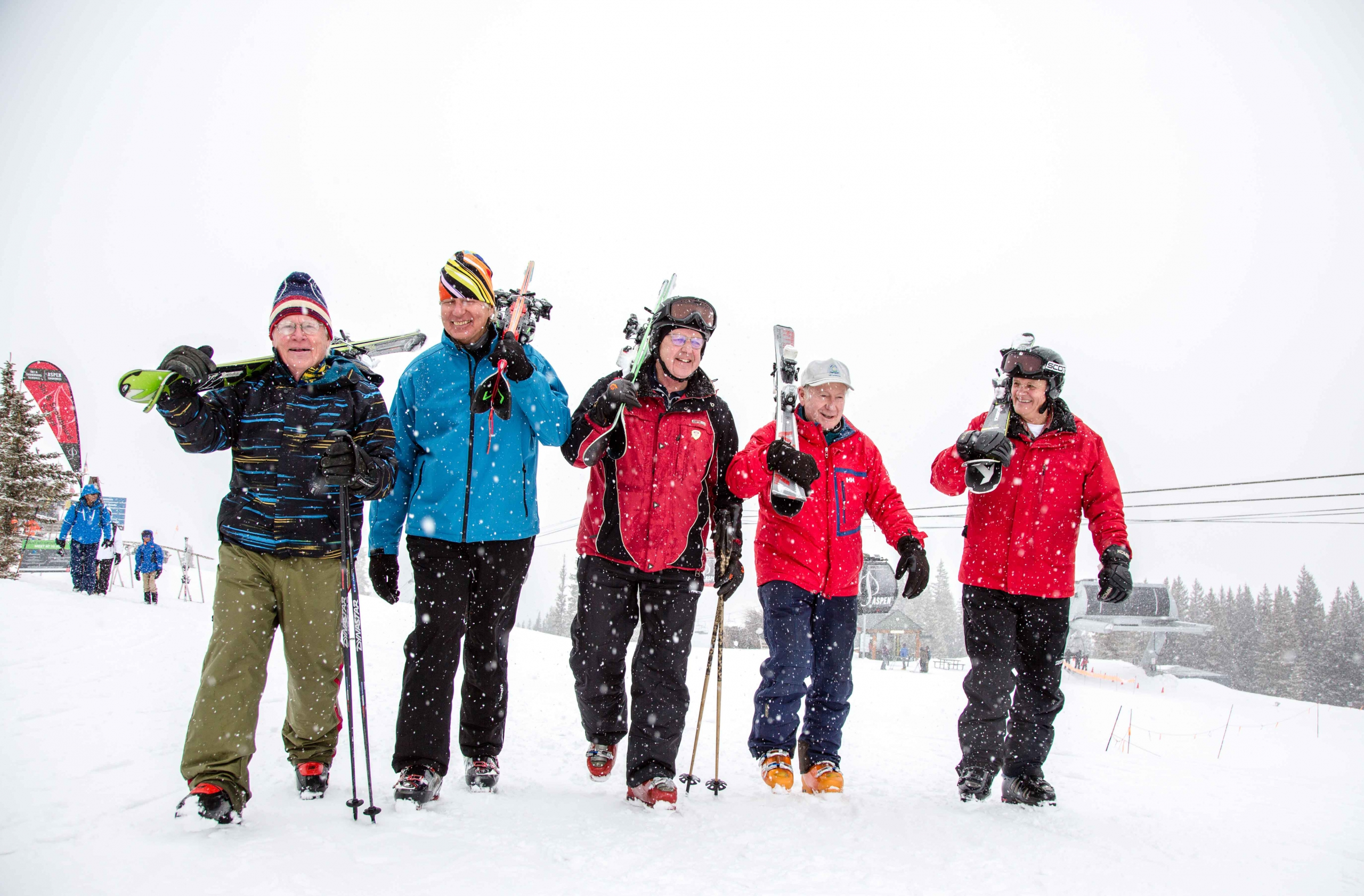 Five senior PSIA members walk from the gondola at Aspen Mountain carrying their skis over their shoulders