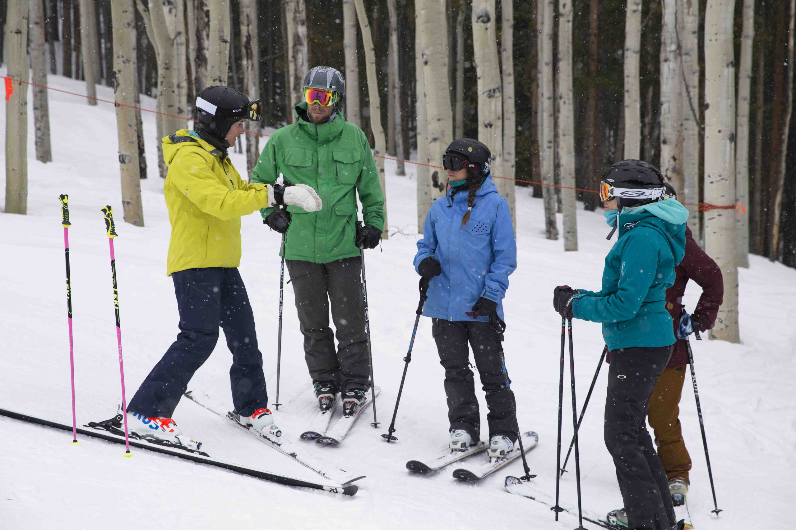 An alpine instructor gives a lesson to a group of three students on the hill