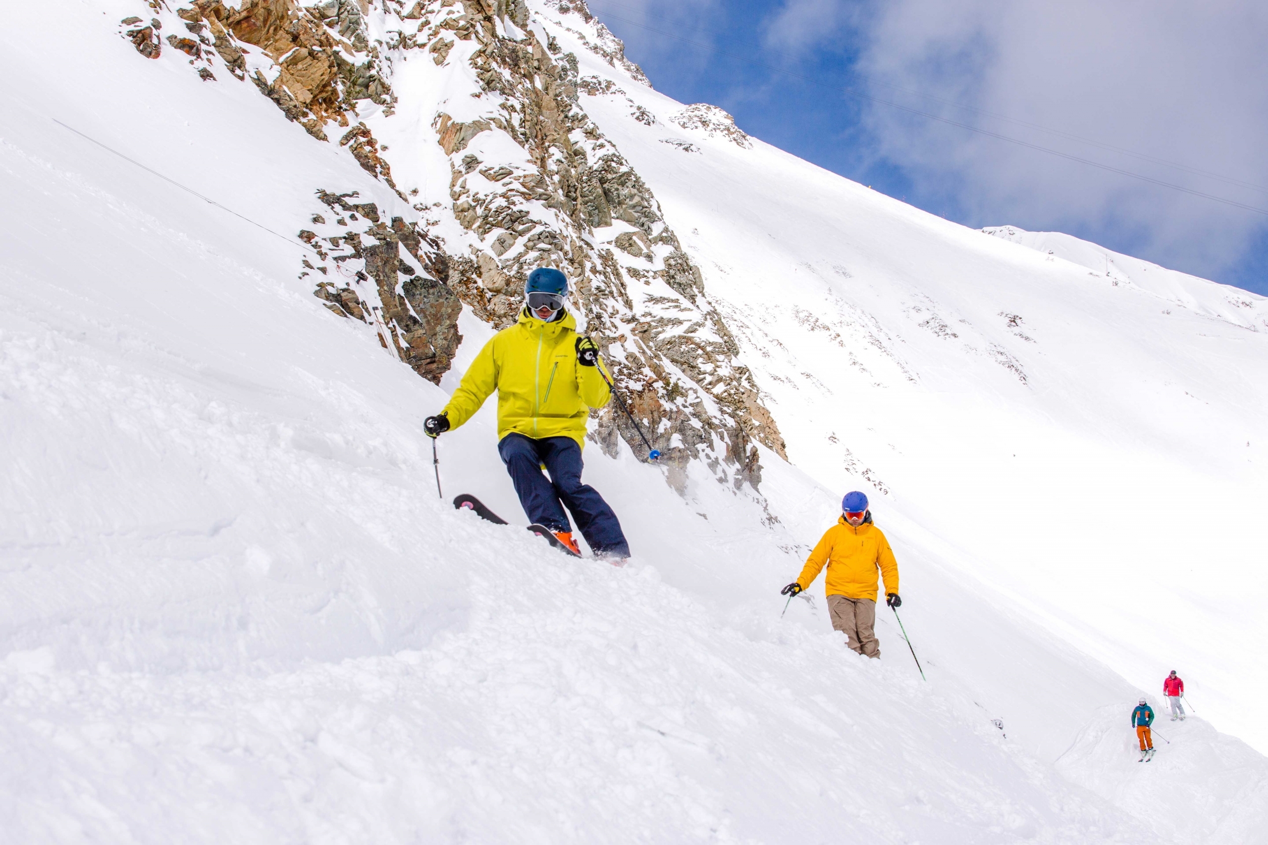 PSIA Alpine Team member Stephen Helfenbein leads a group of skiers as they traverse a steep slope covered in powder