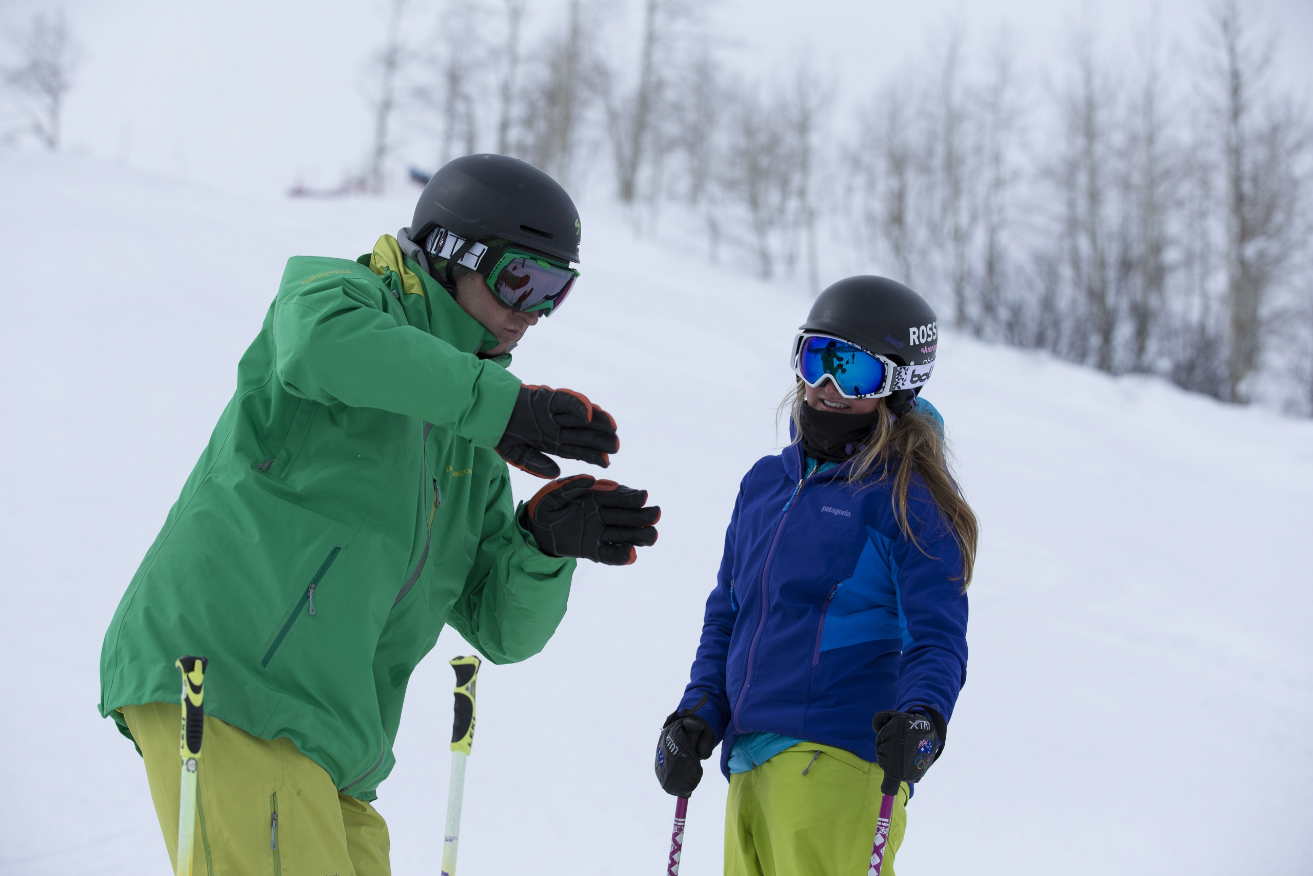 An alpine instructor uses their hands to demonstrate technique to their student