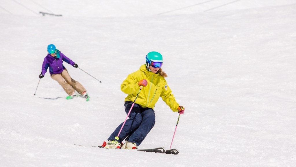 PSIA-AASI National Team Member Robin Barnes demonstrates for her student skiing behind her