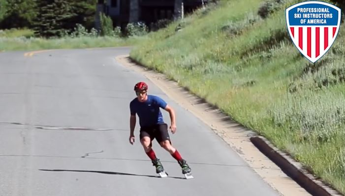 Inline skating down a road, a man on Rollerblades demonstrates similiarities to skiing.