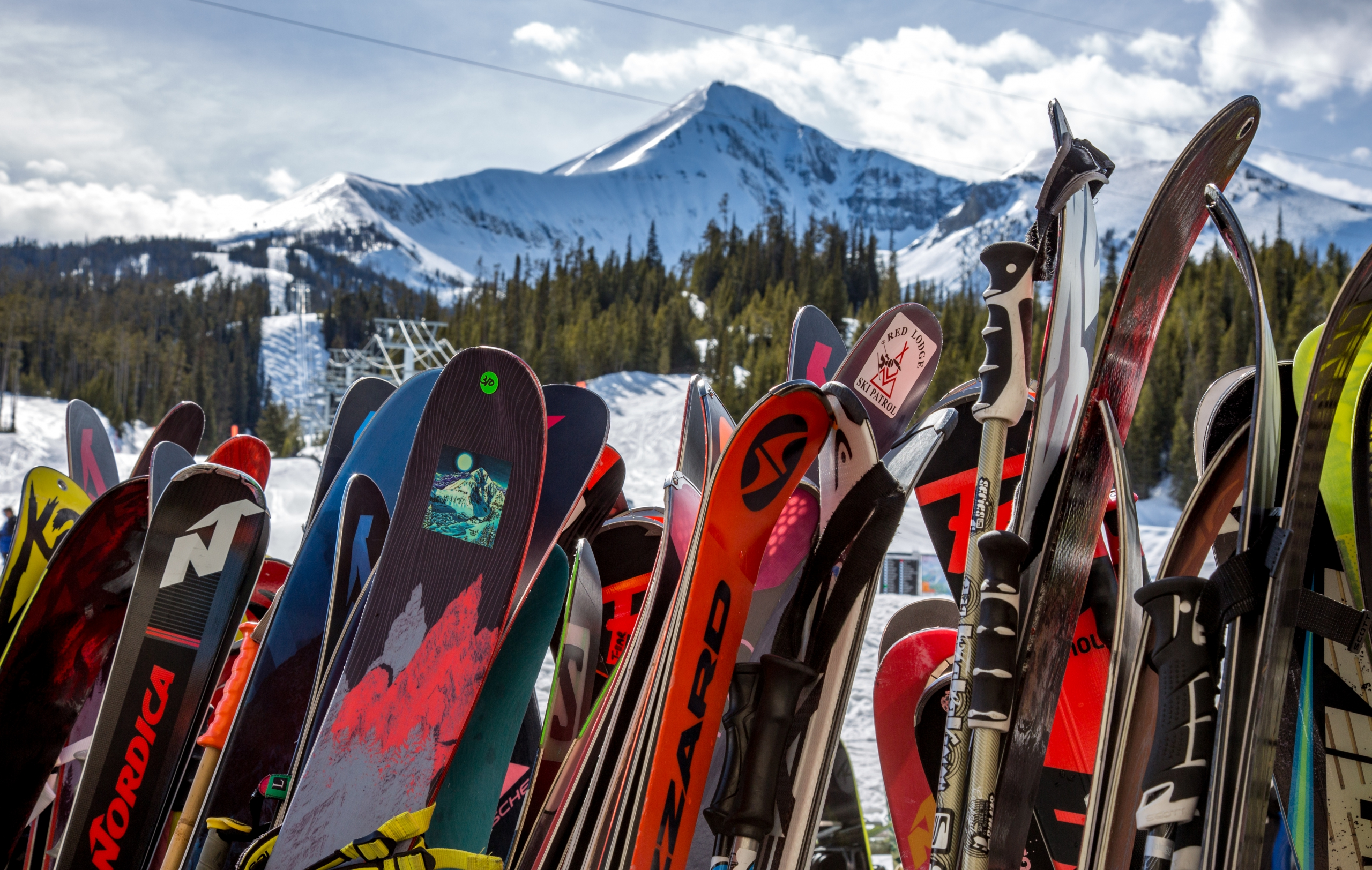 Skis and snowboards rest on a ski rack with Big Sky's Lone Peak in the background