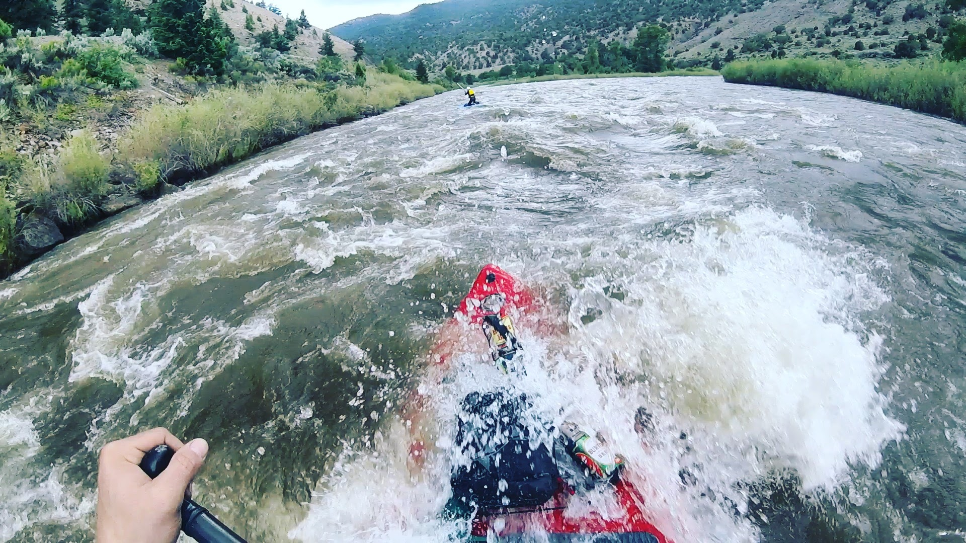 A stand up paddleboarder paddles over a river rapid.