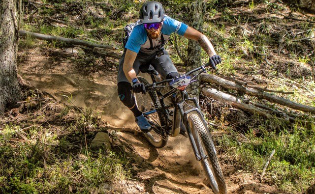 A professional mountain bike instructor rides a downhill course.
