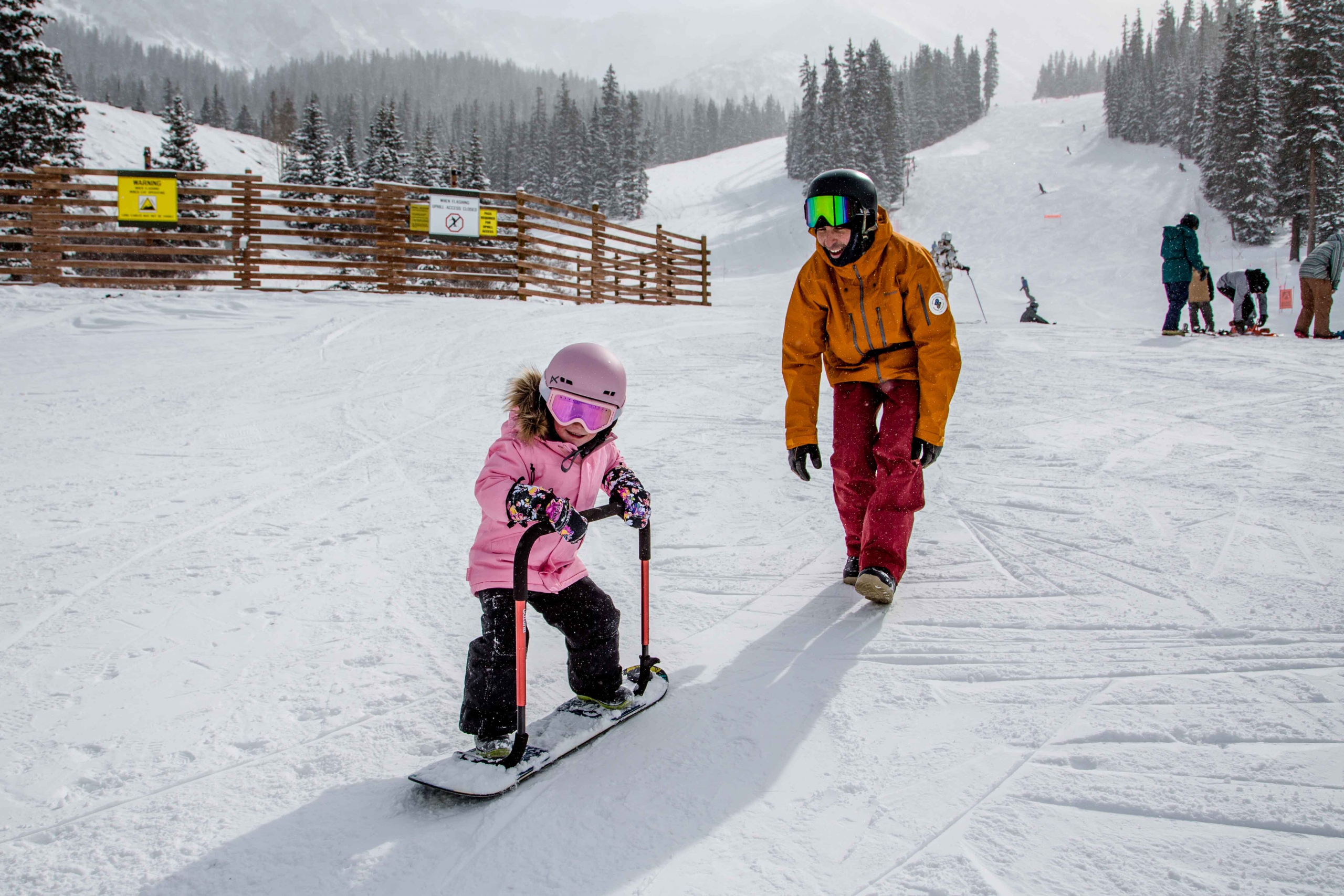 AASI Team member Tony Macri teaches a three-year-old to snowboard.