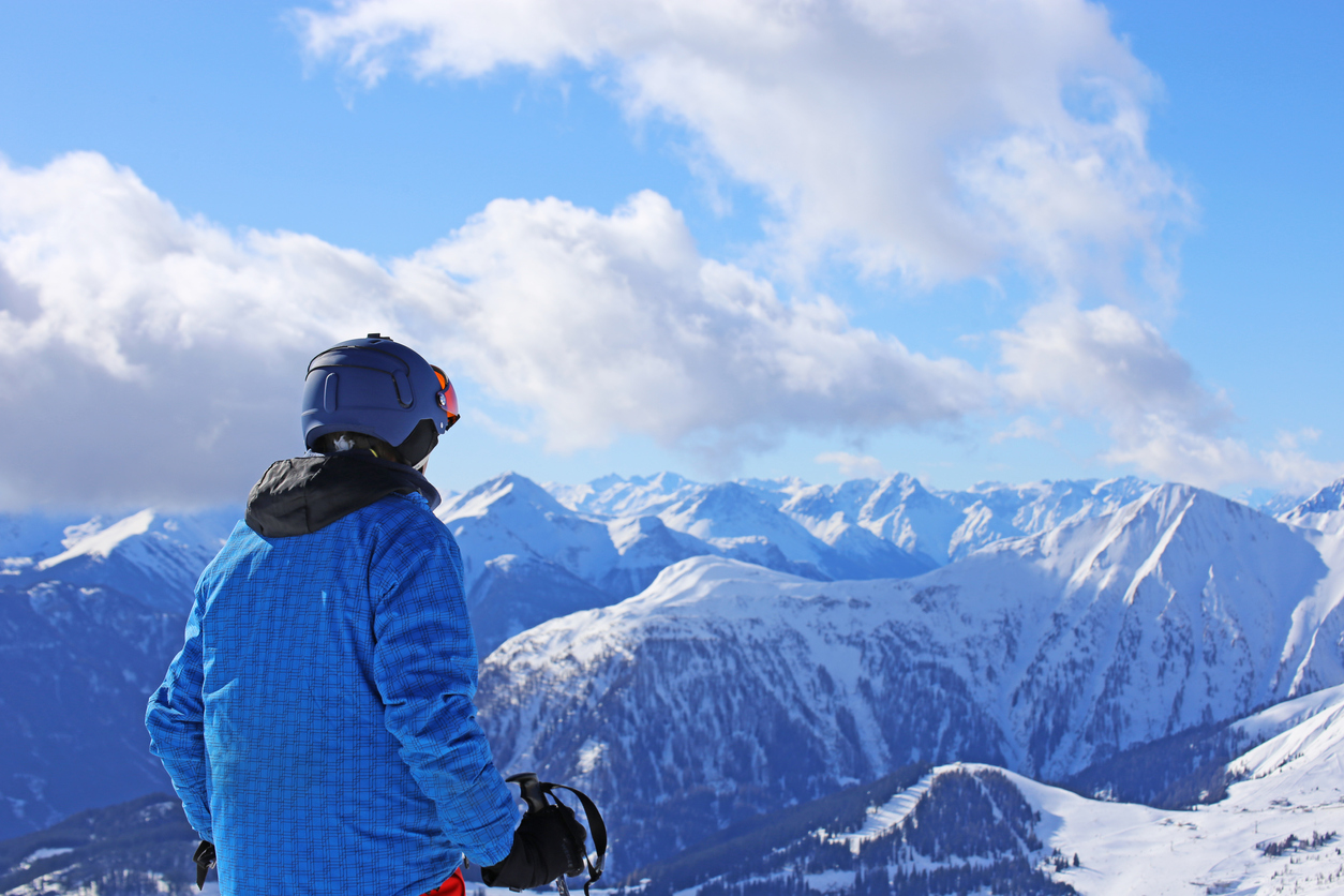 A skier looks at the mountain peaks.