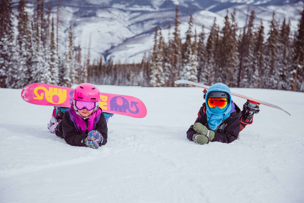 Two kids learn to snowboard