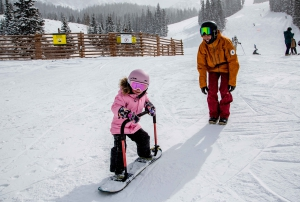 A young girl learns to snowboard on a Burton Riglet board