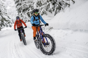 Two people snow bike down a trail