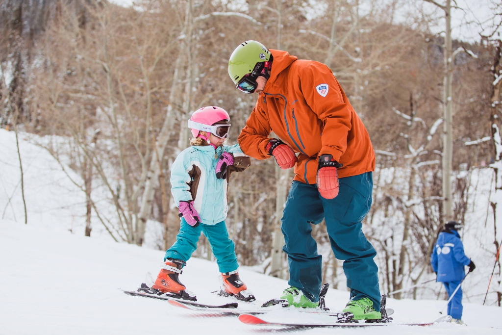 A girl and her ski instructor elbow bump