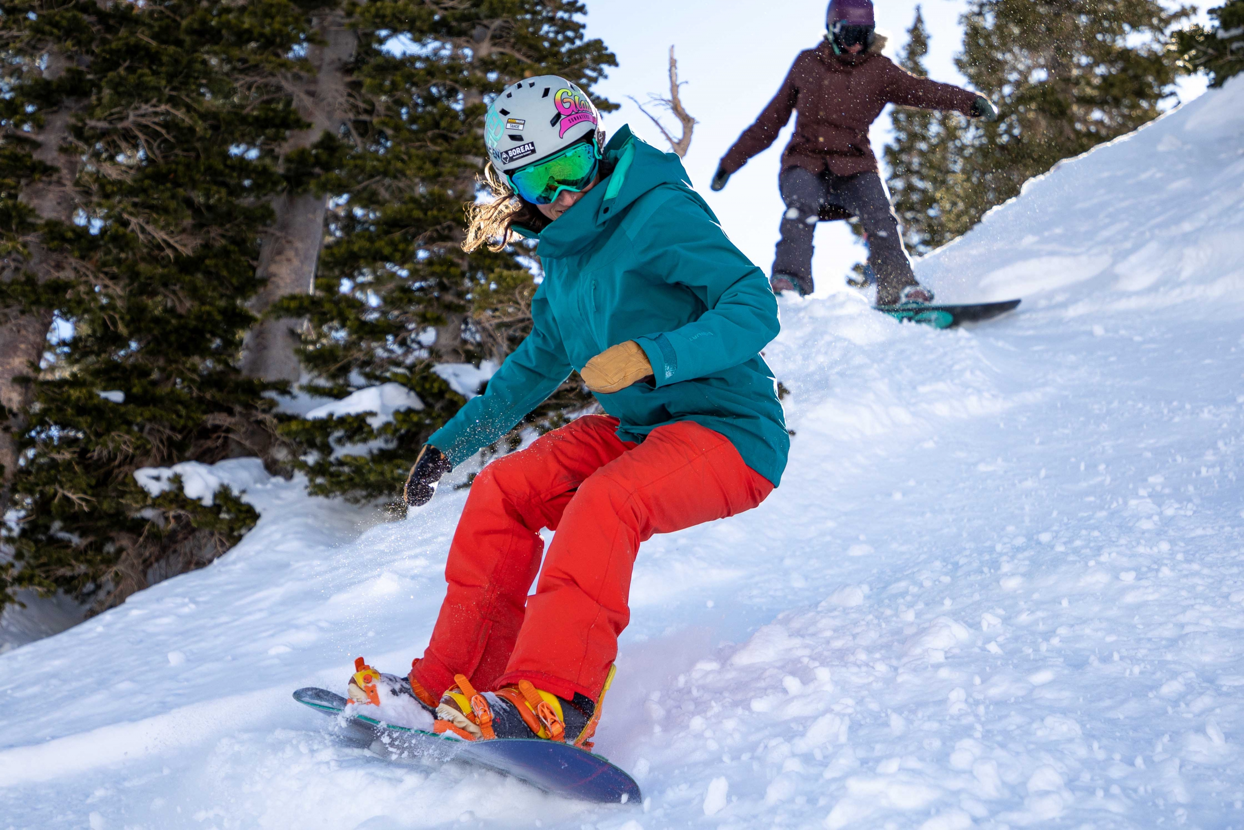 two female snowboarders shred