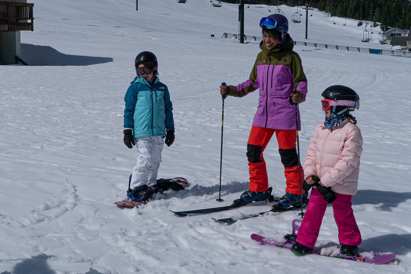 A family skis and snowboard